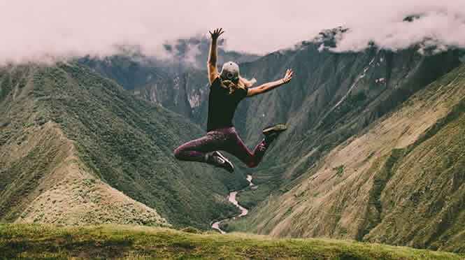 Photo of a woman jumping in the air at the top of a mountain. Other hills and a river are visible below and in the distance.