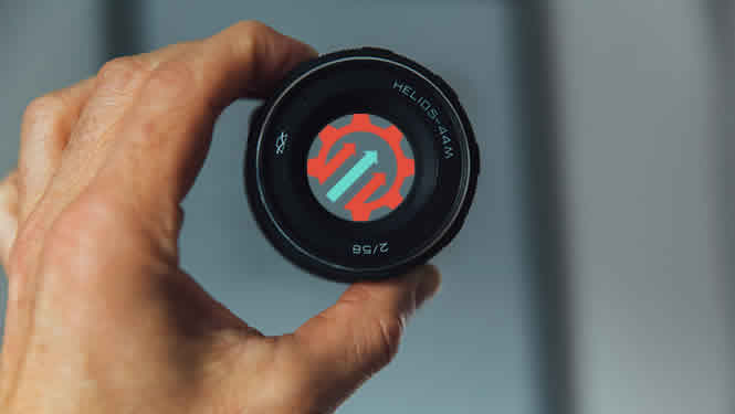 Photo of a man holding the lens of a camera. The geared for growth logo of a gear with upward arrows is in the centre of the lens.