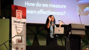 Photo of Josephine Palermo speaking at 1st Conference. There is a screen projected behind her reading, 'How do we measure team effectiveness?'